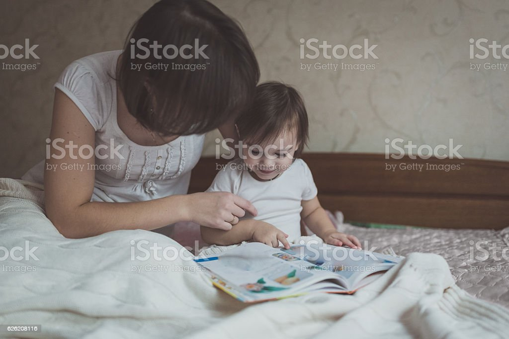 young  mother and daughter Toddler reading  book sitting on  bed stock photo
