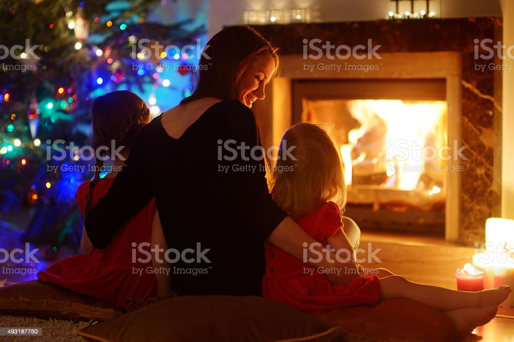 Young mother and daughters sitting by a fireplace on Christmas stock photo