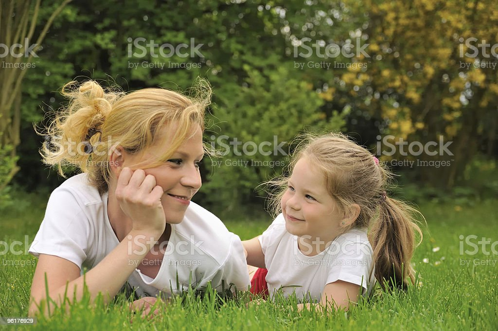Young mother and dauhter laying on the grass royalty-free stock photo