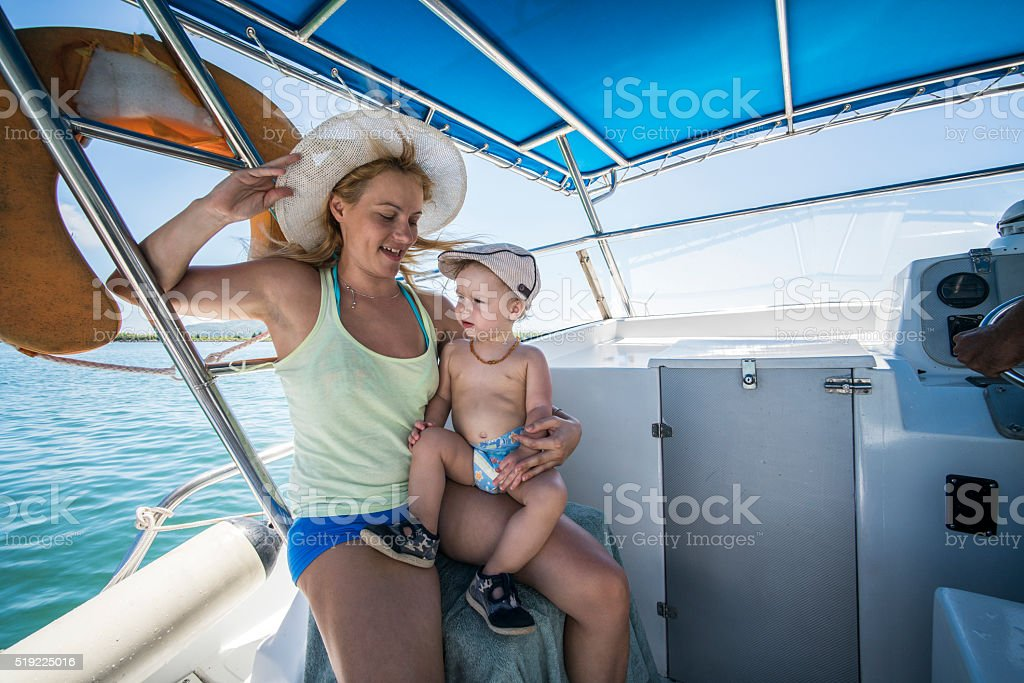 Happy mother and little boy spending a summer day on a boat.