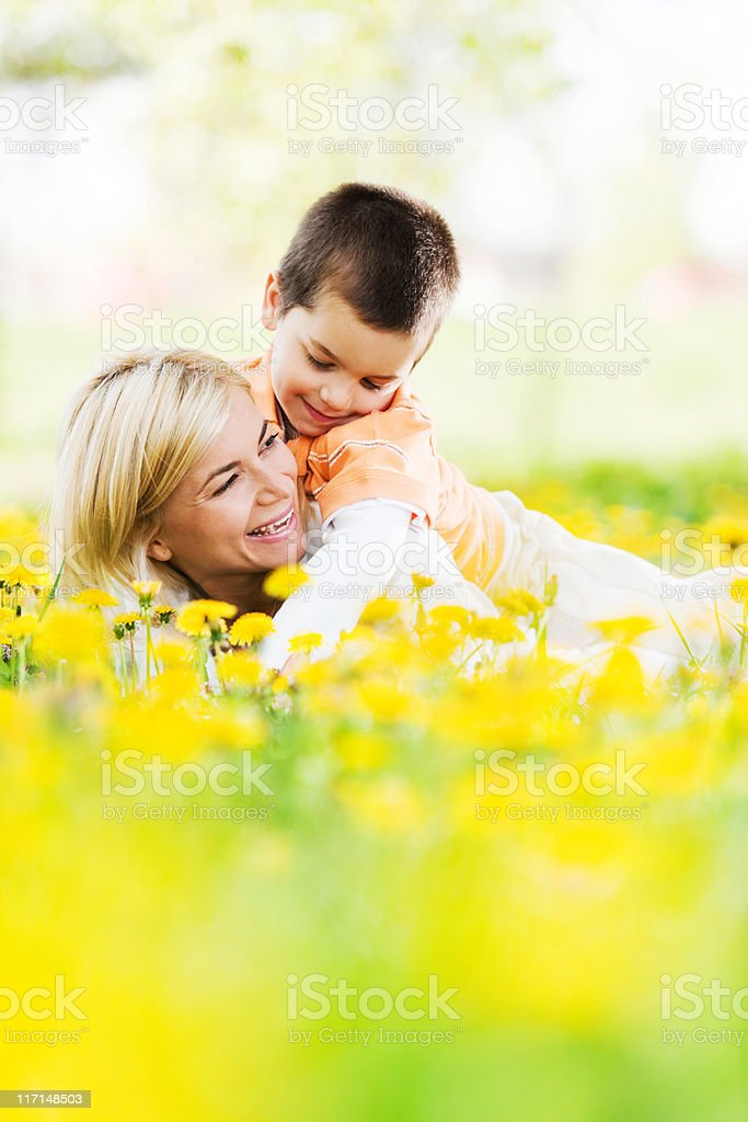 Young mother and her son playing in field of dandelions. royalty-free stock photo