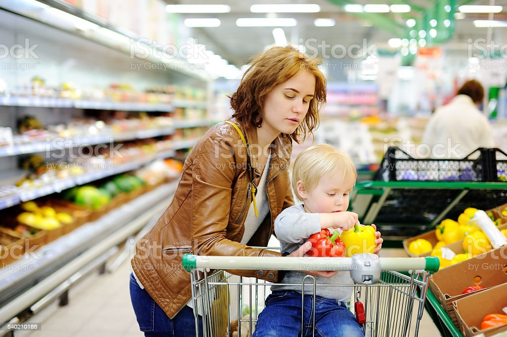 Young mother and her toddler son in a supermarket stock photo