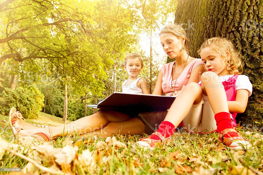 Young mother and her two kids reading together stock photo