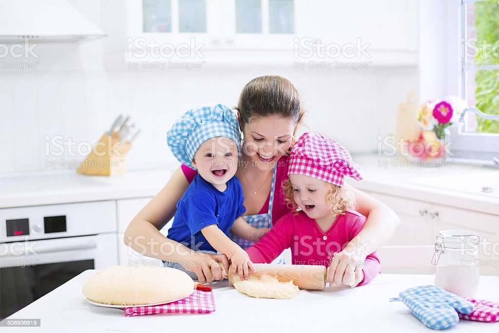 Young mother and kids baking a pie stock photo