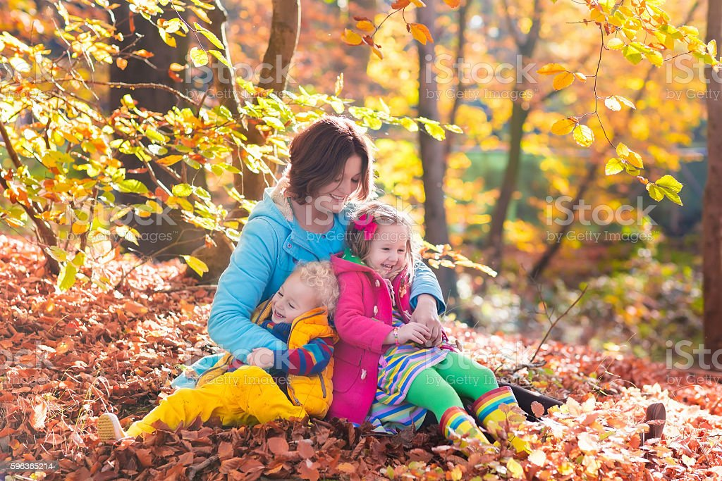 Young mother and kids in autumn park stock photo