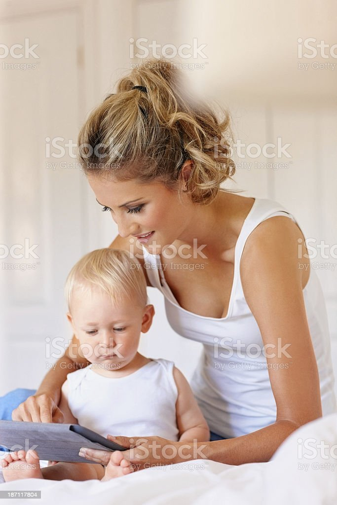 Young mother and little boy with digital tablet on bed royalty-free stock photo