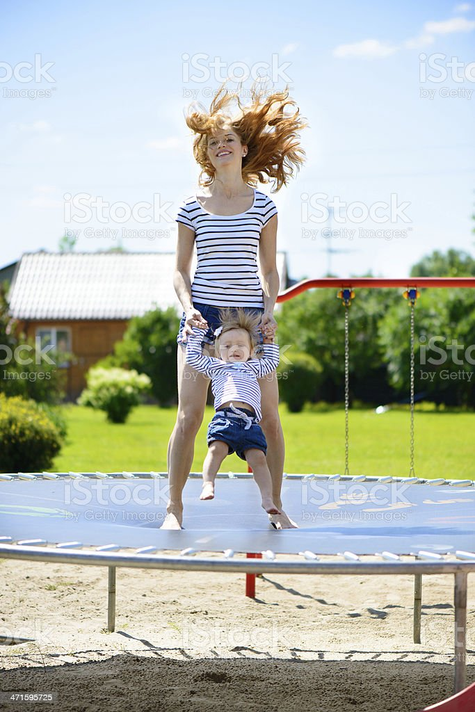 Young mother and little daughter bouncing on trampoline royalty-free stock photo