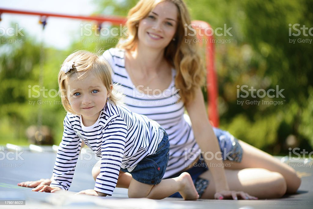 Young mother and little daughter playing at playground royalty-free stock photo