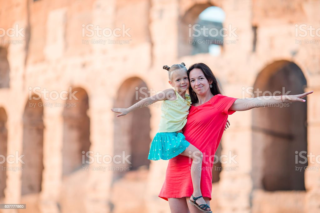 Young mother and little girl exploring Coliseum outside in Rome, stock photo