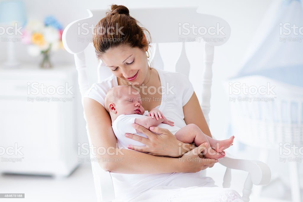 Young mother and newborn baby in white bedroom stock photo
