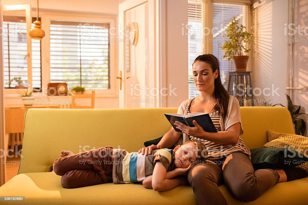 Young mother and tired little boy relaxing at home. stock photo