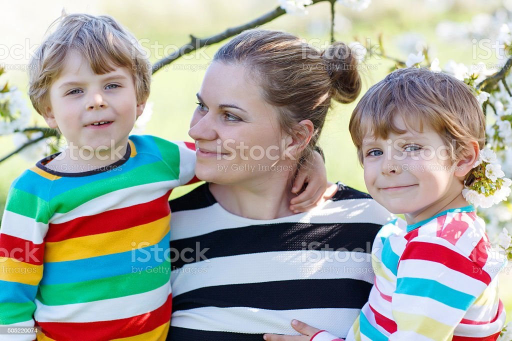 Young mother and two little twins boys in blooming garden stock photo