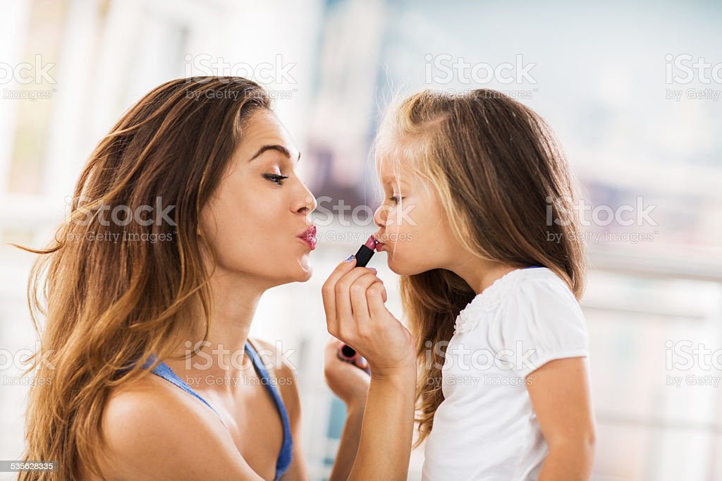 Young mother applying lipstick on her daughter. stock photo