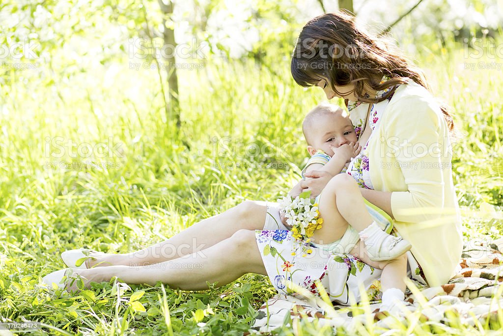 young mother breast feeding her baby outdoors summertime stock photo