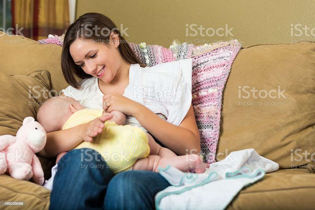 Young mother breastfeeding her baby daughter at home stock photo