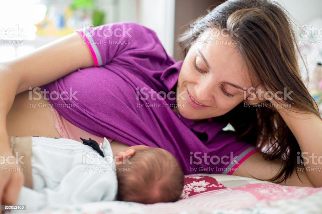 Young mother breastfeeding  her newborn baby boy stock photo