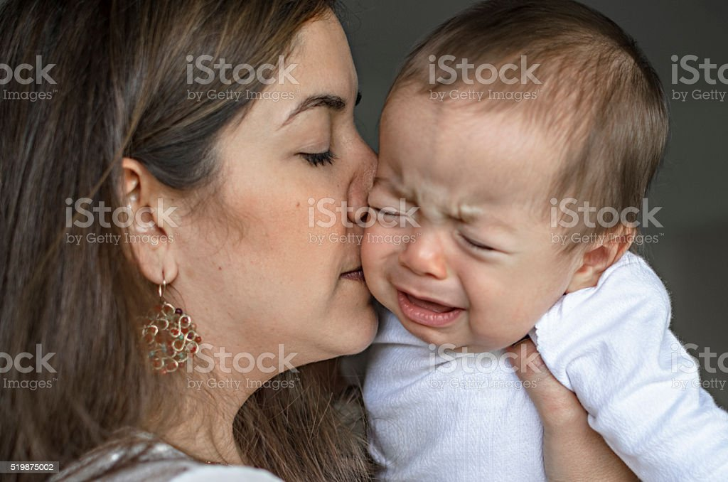 Young mother calming a crying baby stock photo