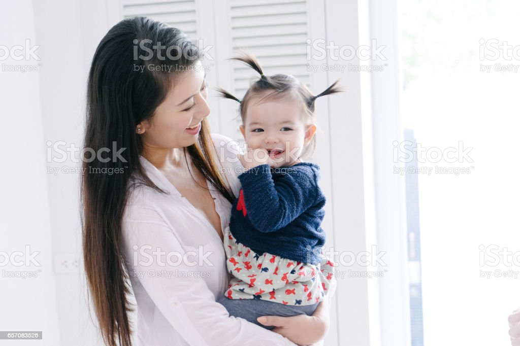 Young mother carrying daughter and playing stock photo