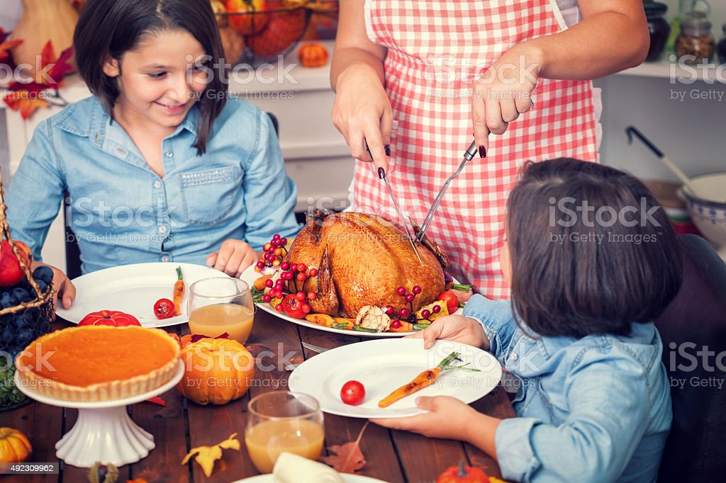 Young mother carving thanksgiving turkey stock photo