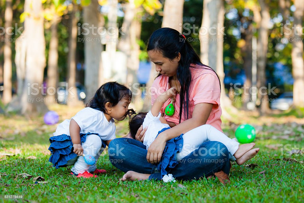 Young mother feeding her baby in the park stock photo