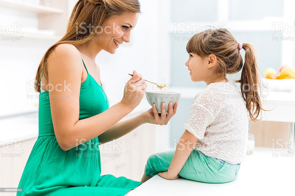 Young mother feeding her daughter in the kitchen. stock photo