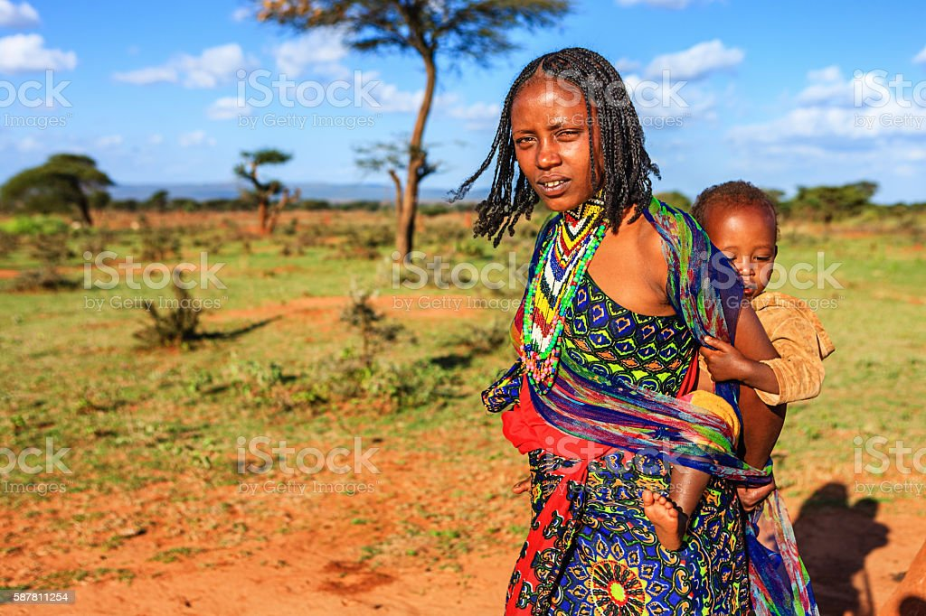 Young mother  from Borana tribe carrying her baby, Ethiopia, Africa stock photo