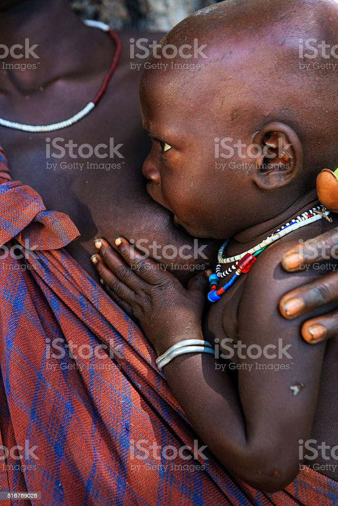 Young mother from Mursi tribe breasfeeding her baby, Ethiopia, Africa stock photo