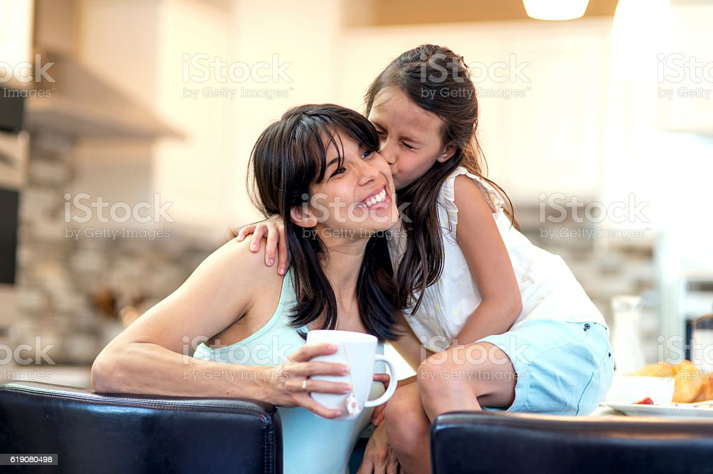 Young mother gets a kiss on the cheek from her daughter stock photo