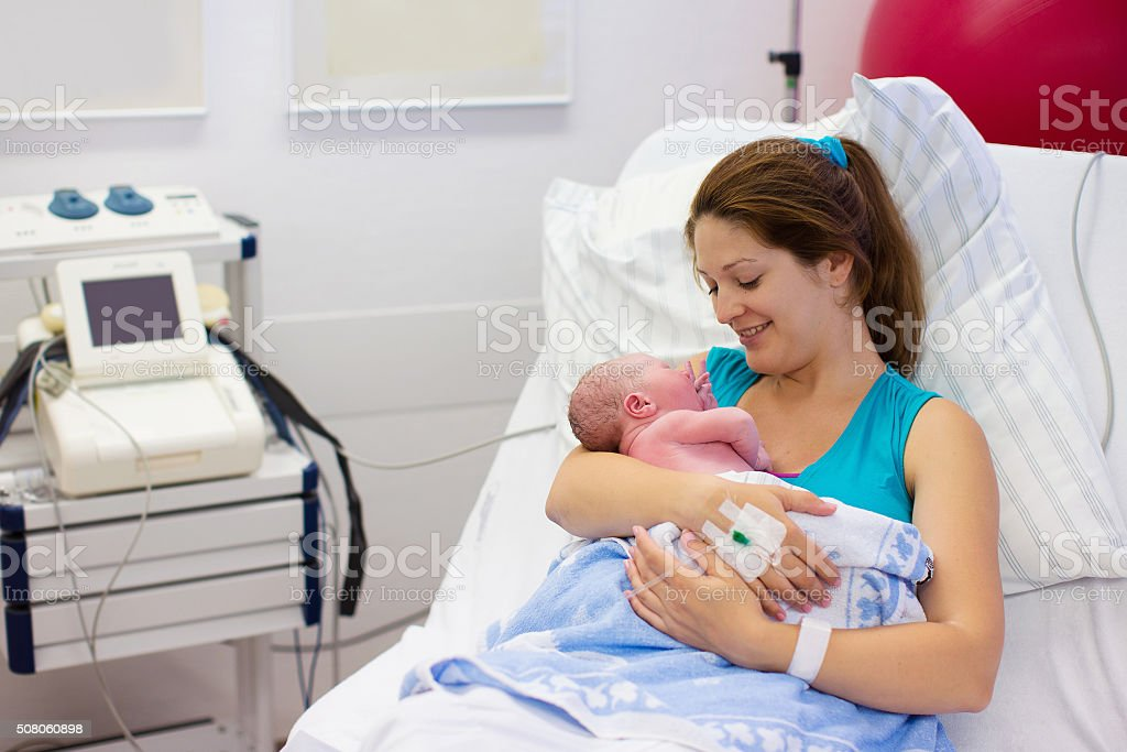 Young mother giving birth to a baby stock photo