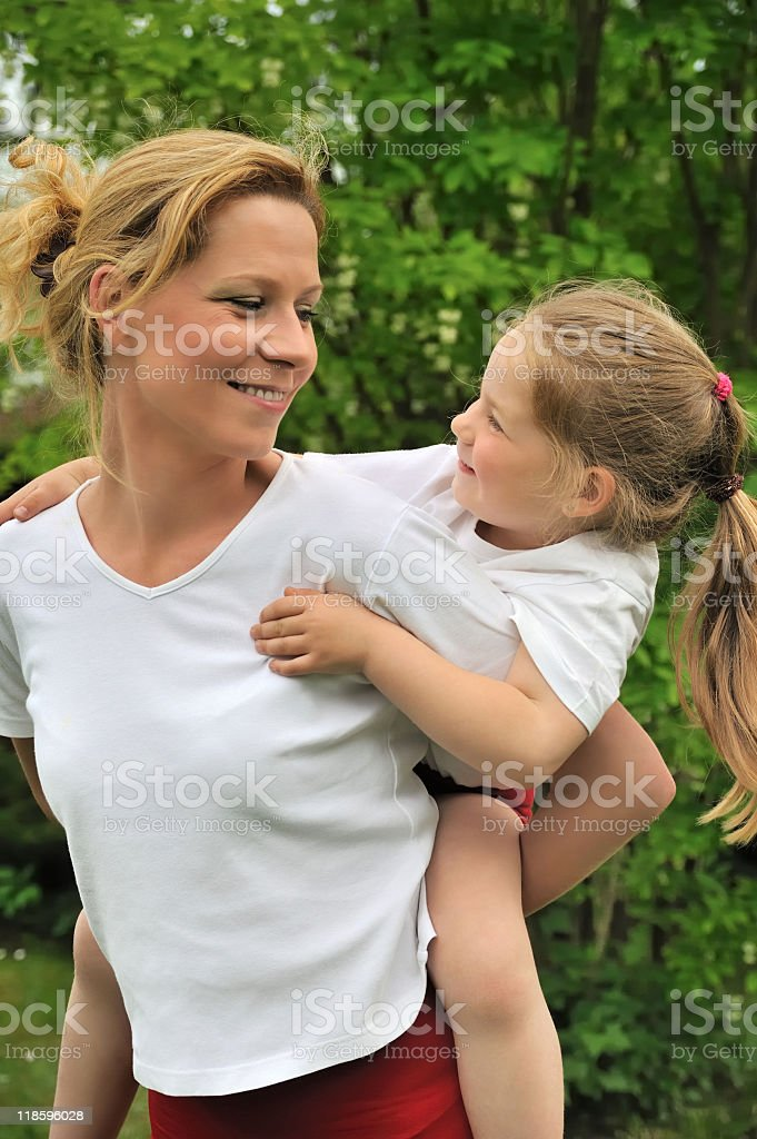 Young mother giving her child piggyback ride royalty-free stock photo
