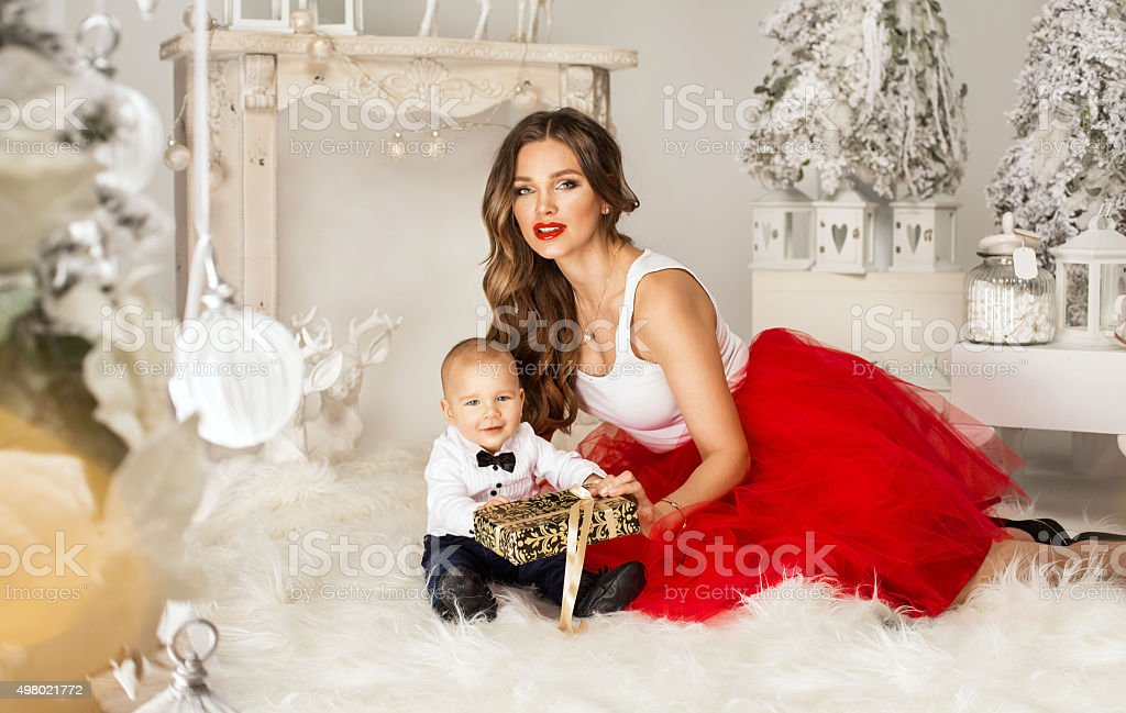 Young mother giving her little boy a Christmas gift stock photo