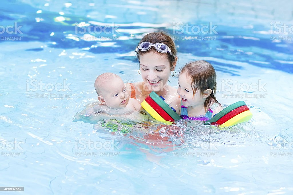 Young mother having fun in swimming pool with two kids stock photo