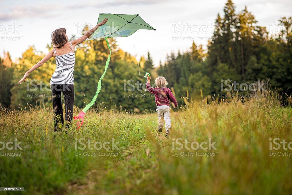 Young mother helping her child to fly a kite stock photo