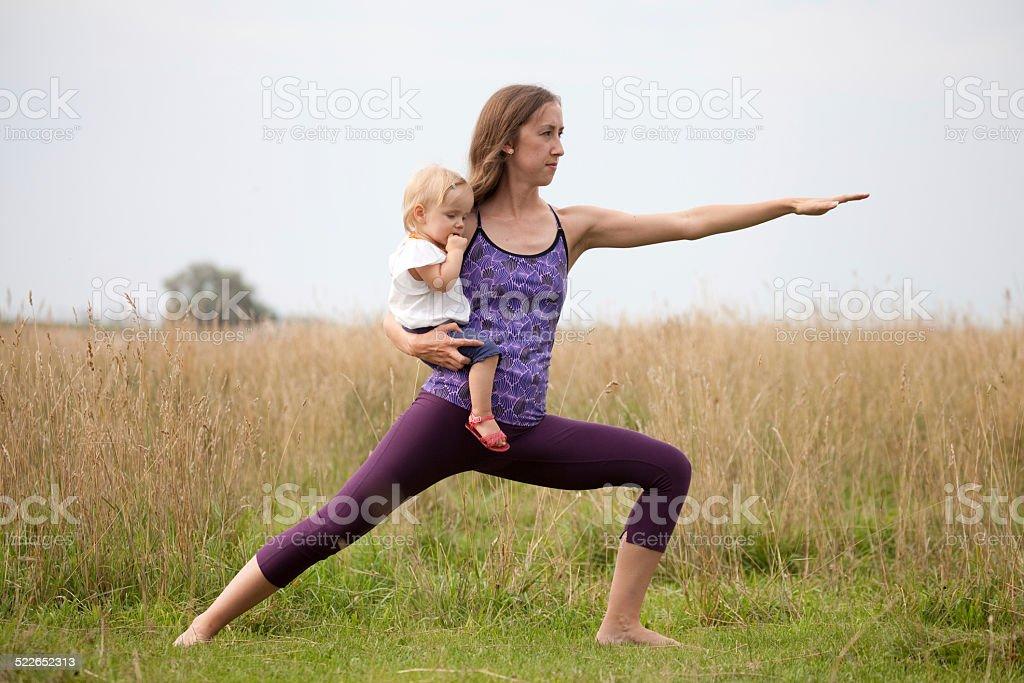 Junge Mutter Holding Baby während Yoga-Übungen im Freien – Foto