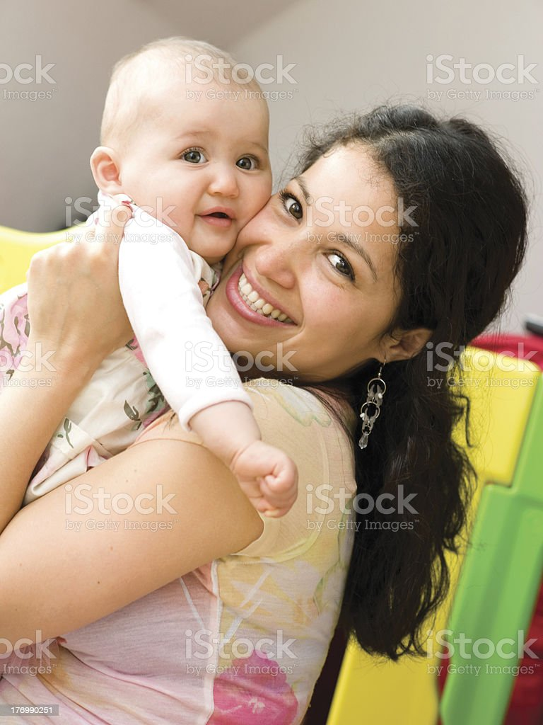 Young mother holding her baby and smiling stock photo