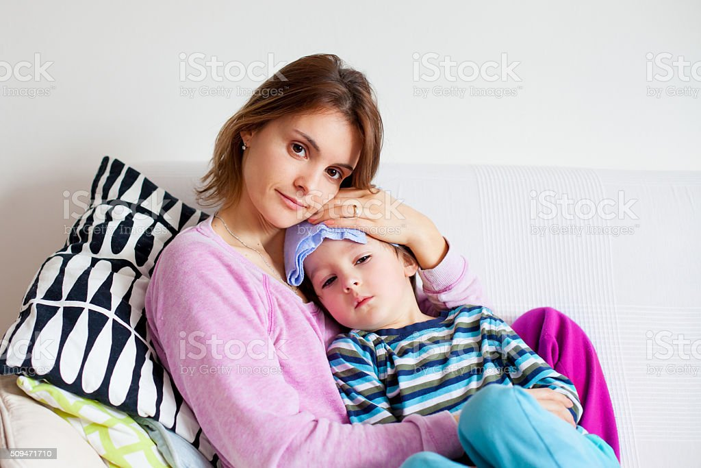 Young mother, holding her little sick boy stock photo