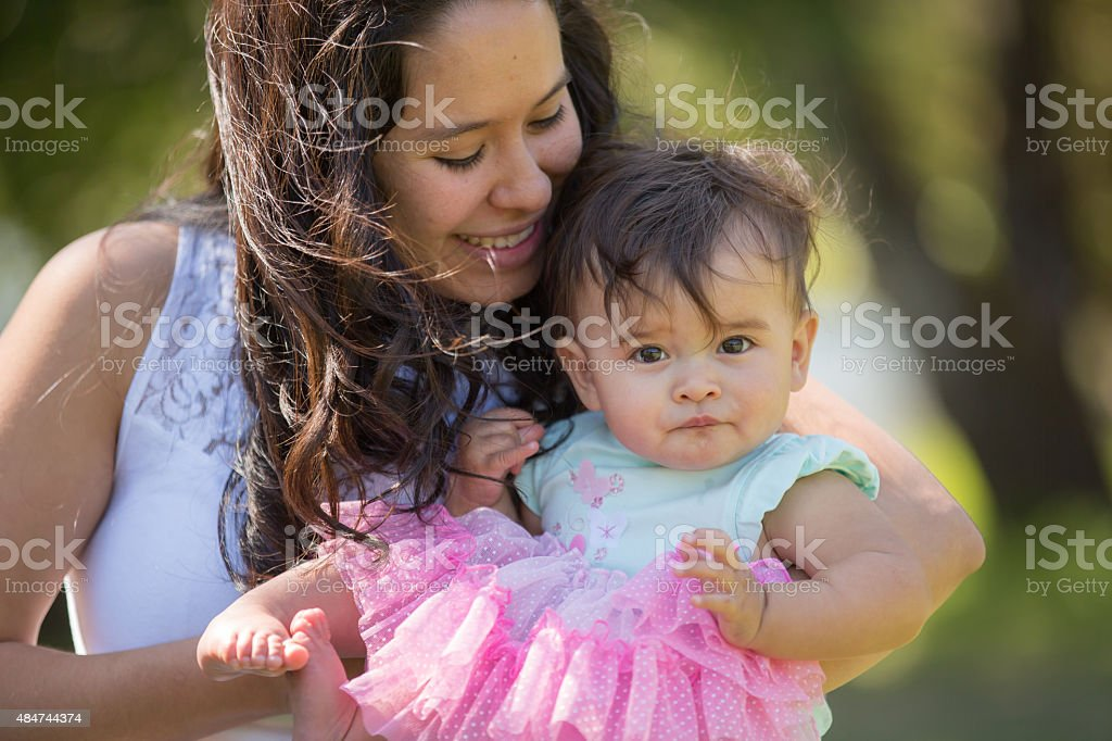 Young mother hugging her baby outdoors stock photo