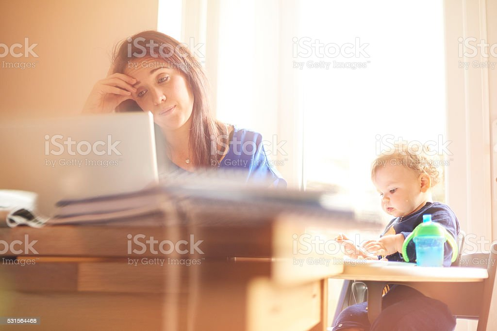 Young mother juggling work and child care stock photo