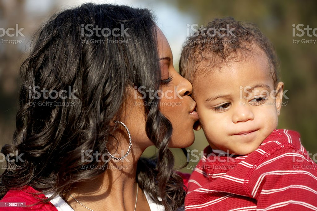 Young mother kissing her toddler son royalty-free stock photo