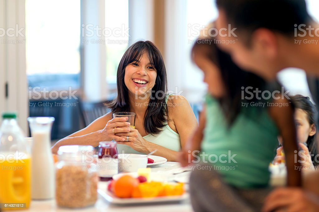 Young mother looking and smiling at her family during breakfast stock photo