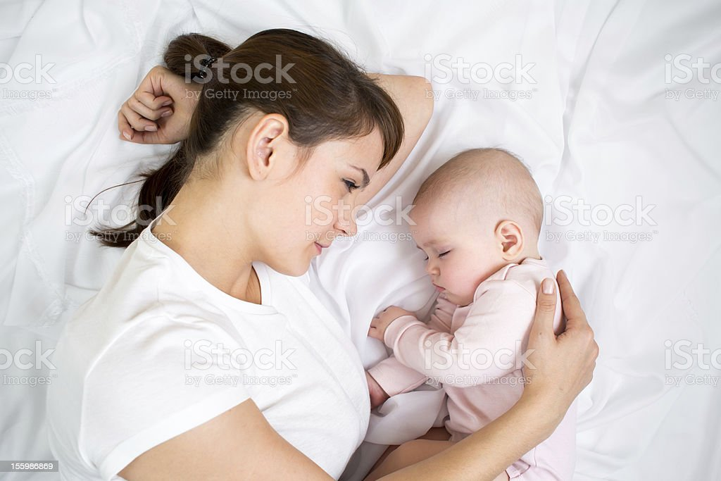 Young mother looking at her sleeping baby girl royalty-free stock photo