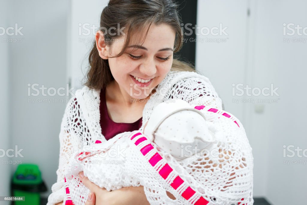 Young mother looking at newborn daughter in the hall of the perinatal center stock photo