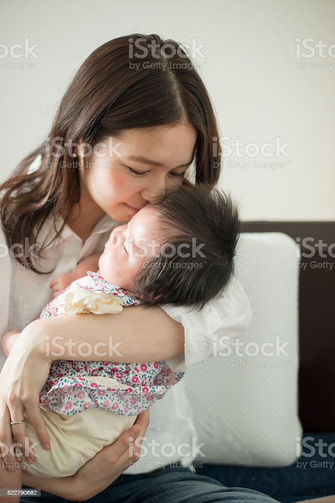 Young mather loving her baby girl at home stock photo