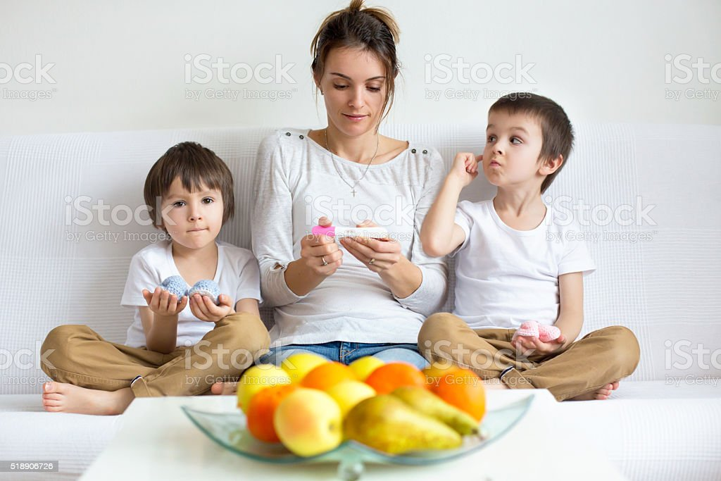 Young mother of two boys, holding positive pregnancy tesт stock photo