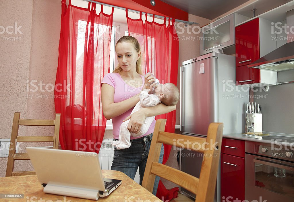 Young mother on kitchen with the laptop royalty-free stock photo