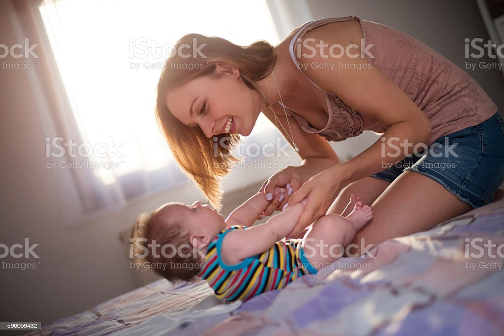 young mother playing with her baby stock photo