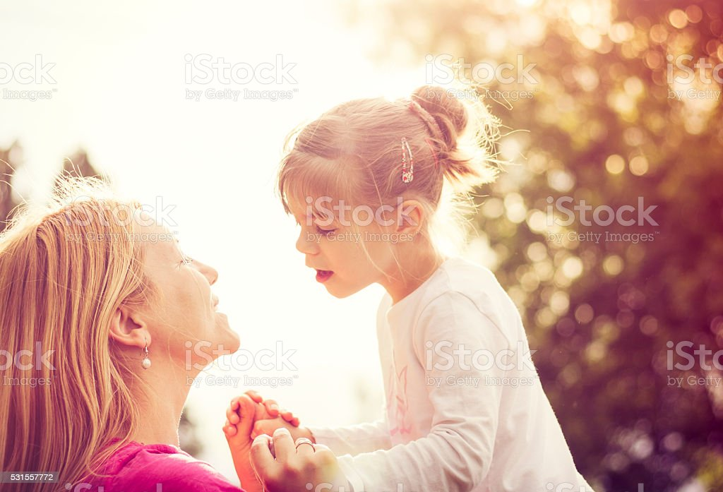Young mother playing with her daughter in nature stock photo