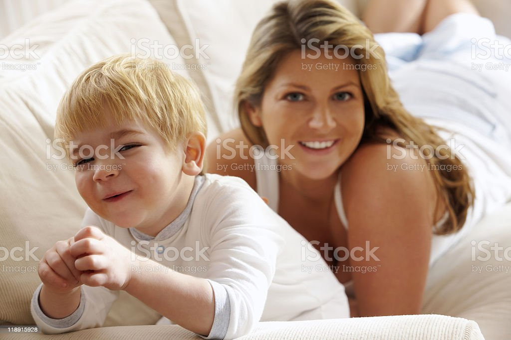 young mother playing with her son on sofa at home royalty-free stock photo