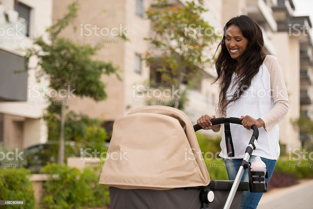 Young mother pushing newborn stroller. stock photo