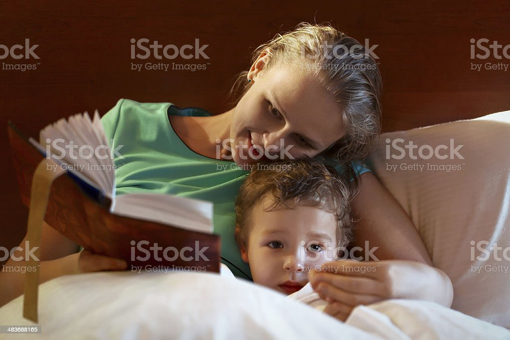 Young mother reading to her child in bed stock photo